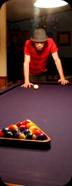 man standing at end of billiards table with bright overhead lighting